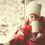 Little girl drinking by the window